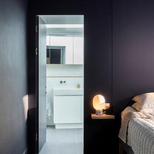 ロンドンの広いモダンスタイルのおしゃれなバスルーム (浴槽なし) (フラットパネル扉のキャビネット、白いキャビネット、バリアフリー、壁掛け式トイレ、白いタイル、セラミックタイル、白い壁、セラミックタイルの床、オーバーカウンターシンク、木製洗面台、グレーの床、開き戸のシャワー、黄色い洗面カウンター、ニッチ、洗面台2つ、独立型洗面台、三角天井、レンガ壁) の写真