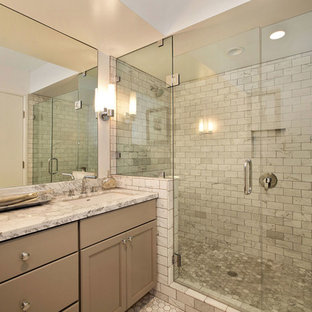 Example of a large trendy master gray tile and mosaic tile pebble tile floor alcove shower design in San Francisco with recessed-panel cabinets, beige cabinets, marble countertops and beige walls