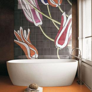 Modern inredning av ett badrum, med ett fristående badkar och orange golv