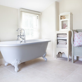 This is an example of a vintage ensuite bathroom in London with freestanding cabinets, white cabinets, a claw-foot bath and beige walls.