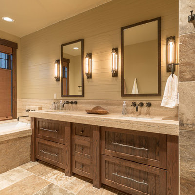 Example of a mountain style master beige tile and stone tile beige floor bathroom design in Seattle with beige walls, shaker cabinets, an undermount tub, an undermount sink and dark wood cabinets