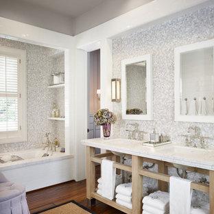 Foto de cuarto de baño principal, campestre, grande, con baldosas y/o azulejos grises, baldosas y/o azulejos blancos, baldosas y/o azulejos en mosaico, suelo de madera oscura, lavabo bajoencimera, armarios abiertos, puertas de armario de madera clara, bañera empotrada, paredes grises y encimera de mármol