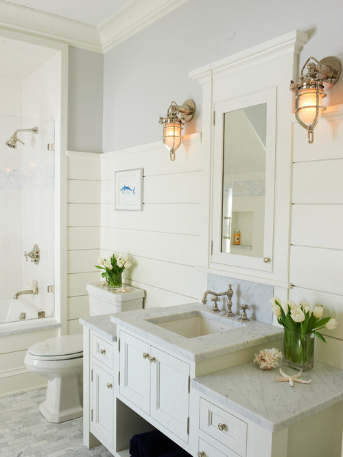 example of a coastal bathroom design in new york with recessed panel cabinets white