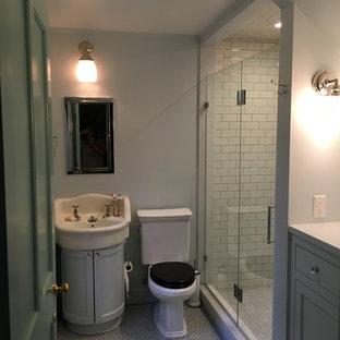 Diseño de cuarto de baño principal, retro, de tamaño medio, con armarios estilo shaker, puertas de armario grises, ducha empotrada, sanitario de dos piezas, baldosas y/o azulejos blancos, baldosas y/o azulejos de cemento, paredes grises, suelo con mosaicos de baldosas, lavabo integrado, encimera de acrílico, suelo multicolor, ducha con puerta con bisagras y encimeras blancas