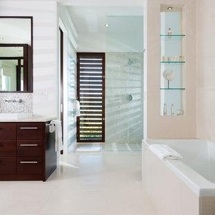 Foto de cuarto de baño infantil, tropical, de tamaño medio, con armarios tipo mueble, puertas de armario de madera en tonos medios, bañera encastrada, ducha abierta, sanitario de pared, baldosas y/o azulejos blancos, baldosas y/o azulejos de cerámica, paredes beige y suelo de piedra caliza