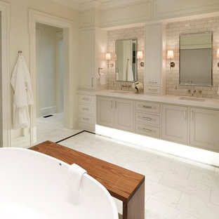 Example of a large transitional master white tile and marble tile marble floor and white floor bathroom design in Salt Lake City with recessed-panel cabinets, white cabinets, white walls, an undermount sink, solid surface countertops and a hinged shower door