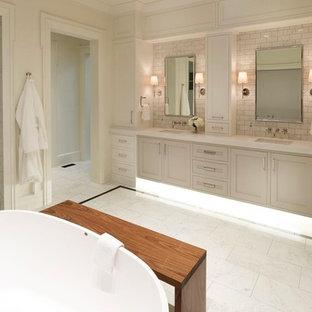Bild på ett stort vintage en-suite badrum, med luckor med infälld panel, vita skåp, ett fristående badkar, en dusch i en alkov, vit kakel, marmorkakel, vita väggar, marmorgolv, ett undermonterad handfat, bänkskiva i akrylsten, vitt golv och dusch med gångjärnsdörr