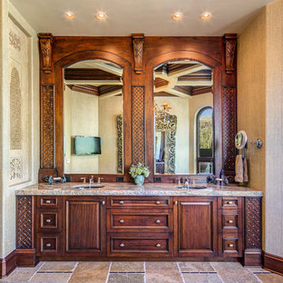Example of a tuscan master multicolored tile slate floor alcove shower design in Phoenix with an undermount sink, raised-panel cabinets, dark wood cabinets, glass countertops and beige walls
