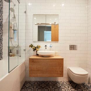 Неиссякаемый источник вдохновения для домашнего уюта: маленькая главная ванная комната в современном стиле с фасадами цвета дерева среднего тона, душем над ванной, инсталляцией, синей плиткой, белой плиткой, белыми стенами, полом из керамической плитки, настольной раковиной, столешницей из дерева, плоскими фасадами, ванной в нише, открытым душем и коричневой столешницей