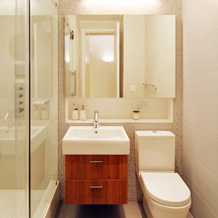 Design ideas for a small modern shower room in New York with an alcove shower, an integrated sink, medium wood cabinets, beige tiles, white tiles, ceramic flooring, a two-piece toilet, flat-panel cabinets, ceramic tiles, beige walls, solid surface worktops, beige floors and a sliding door.