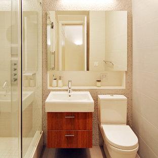Стильный дизайн: маленькая ванная комната в стиле модернизм с душем в нише, монолитной раковиной, фасадами цвета дерева среднего тона, бежевой плиткой, белой плиткой, полом из керамической плитки, душевой кабиной, раздельным унитазом, плоскими фасадами, керамической плиткой, бежевыми стенами, столешницей из искусственного камня, бежевым полом, душем с раздвижными дверями и нишей - последний тренд
