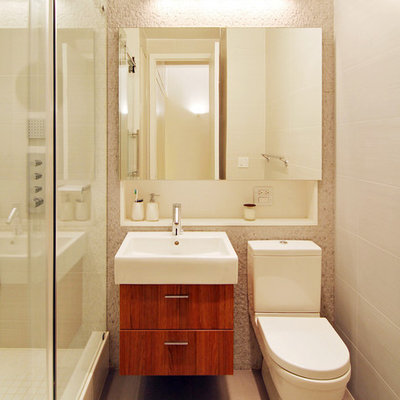 Example of a small minimalist 3/4 beige tile, white tile and ceramic tile ceramic tile and beige floor bathroom design in New York with an integrated sink, medium tone wood cabinets, a two-piece toilet, flat-panel cabinets, beige walls and solid surface countertops