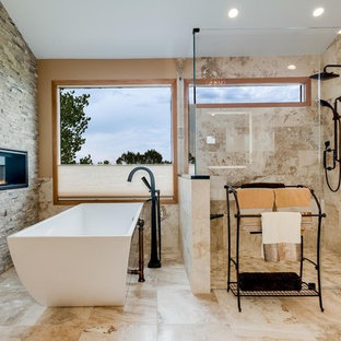 Inspiration for a large mediterranean ensuite bathroom in Denver with glass-front cabinets, beige cabinets, a freestanding bath, a built-in shower, beige tiles, travertine tiles, beige walls, travertine flooring, a submerged sink, quartz worktops, beige floors and a hinged door.