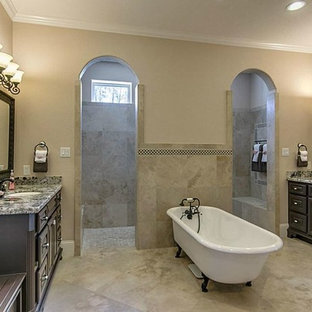 Inspiration for a large mediterranean ensuite bathroom in Houston with raised-panel cabinets, dark wood cabinets, granite worktops, a claw-foot bath, a walk-in shower, beige tiles, ceramic tiles, beige walls and travertine flooring.