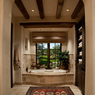 Mid-sized tuscan master beige tile and stone tile limestone floor bathroom photo in Phoenix with raised-panel cabinets, dark wood cabinets, an undermount tub and beige walls