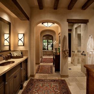 Пример оригинального дизайна интерьера: главная ванная комната среднего размера в средиземноморском стиле с фасадами с выступающей филенкой, темными деревянными фасадами, столешницей из известняка, бежевой плиткой, душем в нише, врезной раковиной, бежевыми стенами, полом из известняка, полновстраиваемой ванной, унитазом-моноблоком и плиткой из известняка