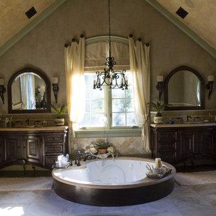 Ispirazione per una stanza da bagno mediterranea con ante in legno bruno, vasca idromassaggio e piastrelle beige