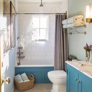 Idee per una stanza da bagno country con ante in stile shaker, ante blu, vasca ad alcova, vasca/doccia, WC a due pezzi, piastrelle bianche, piastrelle diamantate, lavabo sottopiano, top in marmo, pareti blu, doccia con tenda, top bianco, pavimento in pietra calcarea e pavimento beige