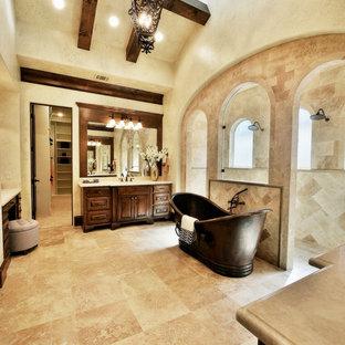 Пример оригинального дизайна: большая главная ванная комната в средиземноморском стиле с фасадами с выступающей филенкой, фасадами цвета дерева среднего тона, отдельно стоящей ванной, двойным душем, бежевой плиткой, керамической плиткой, бежевыми стенами, полом из травертина, врезной раковиной, мраморной столешницей, бежевым полом и открытым душем