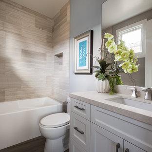 Esempio di una piccola stanza da bagno con doccia contemporanea con lavabo sottopiano, ante in stile shaker, ante bianche, vasca ad alcova, WC monopezzo, piastrelle beige, piastrelle in gres porcellanato, pareti grigie, vasca/doccia, pavimento in vinile e top in superficie solida