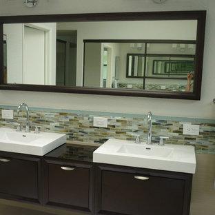 Modelo de cuarto de baño principal, actual, de tamaño medio, con puertas de armario de madera en tonos medios, encimera de vidrio, baldosas y/o azulejos de porcelana, armarios con paneles lisos, bañera exenta, ducha esquinera, baldosas y/o azulejos beige, paredes grises, suelo de baldosas de porcelana, lavabo integrado, suelo beige y ducha con puerta con bisagras