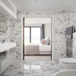 Large contemporary ensuite bathroom in Gloucestershire with a one-piece toilet, black and white tiles, multi-coloured walls, marble flooring, a wall-mounted sink, multi-coloured floors and white worktops.