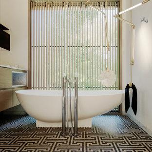 Foto de cuarto de baño moderno con armarios con paneles lisos, puertas de armario de madera oscura, bañera exenta, paredes blancas, suelo con mosaicos de baldosas y suelo multicolor