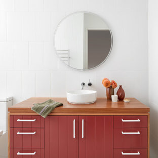 Large contemporary master bathroom in Melbourne with red cabinets, a two-piece toilet, white tile, white walls, terrazzo floors, wood benchtops, brown benchtops, a single vanity, a freestanding vanity, flat-panel cabinets, a vessel sink, grey floor and vaulted.