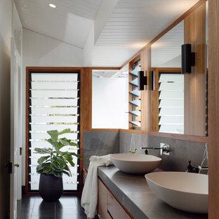 Aménagement d'une salle de bain principale contemporaine avec un placard à porte plane, des portes de placard en bois brun, un mur blanc, une vasque, un sol noir, un plan de toilette gris, meuble double vasque, meuble-lavabo suspendu, un plafond en lambris de bois, un plafond voûté et du lambris de bois.