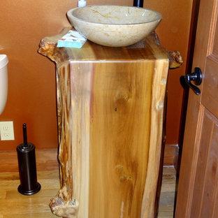 Esempio di una piccola stanza da bagno con doccia stile rurale con lavabo a bacinella, consolle stile comò, ante in legno chiaro, vasca ad alcova, vasca/doccia, WC a due pezzi, pareti arancioni e parquet chiaro