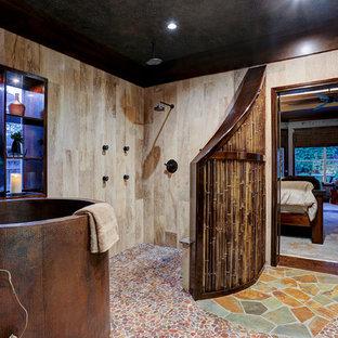 Modelo de cuarto de baño principal, asiático, con bañera japonesa, ducha abierta, paredes beige, suelo de baldosas tipo guijarro y ducha abierta