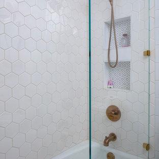 Bild på ett mellanstort vintage vit vitt badrum för barn, med luckor med infälld panel, vita skåp, ett badkar i en alkov, en dusch/badkar-kombination, en toalettstol med separat cisternkåpa, vit kakel, keramikplattor, vita väggar, klinkergolv i keramik, ett undermonterad handfat, marmorbänkskiva, flerfärgat golv och med dusch som är öppen