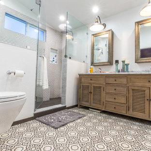 Diseño de cuarto de baño principal, actual, de tamaño medio, con armarios con puertas mallorquinas, puertas de armario con efecto envejecido, ducha doble, sanitario de pared, baldosas y/o azulejos grises, paredes blancas, suelo de azulejos de cemento, lavabo bajoencimera, encimera de granito, ducha con puerta con bisagras y encimeras grises