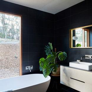 Ispirazione per una stanza da bagno padronale contemporanea con ante lisce, ante bianche, vasca freestanding, piastrelle nere, lavabo a bacinella e pavimento nero