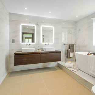 Inspiration for a contemporary ensuite bathroom in London with a freestanding bath, a built-in shower, flat-panel cabinets, dark wood cabinets, a one-piece toilet, grey tiles, grey walls, a vessel sink, wooden worktops, a hinged door and brown worktops.