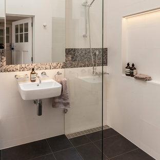 Foto di una piccola stanza da bagno con doccia minimalista con ante di vetro, doccia alcova, WC sospeso, piastrelle bianche, piastrelle di cemento, pareti bianche, pavimento con piastrelle in ceramica, lavabo sospeso, pavimento grigio e doccia aperta