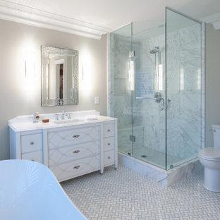 Diseño de cuarto de baño principal, tradicional renovado, grande, con armarios tipo mueble, puertas de armario blancas, bañera exenta, ducha esquinera, baldosas y/o azulejos grises, paredes grises, suelo de baldosas de porcelana, lavabo bajoencimera, suelo gris y encimeras turquesas