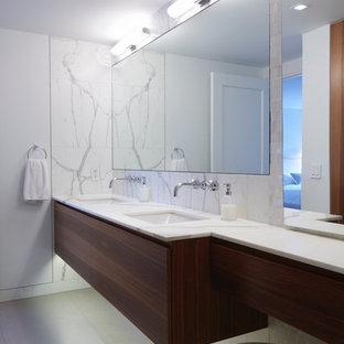 Cette image montre une salle de bain principale minimaliste de taille moyenne avec un placard à porte plane, des portes de placard en bois sombre, un WC suspendu, un carrelage de pierre, un plan de toilette en marbre, une baignoire encastrée, un mur gris, béton au sol, un lavabo encastré et un sol gris.