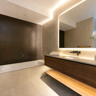 Contemporary bathroom in Brisbane with flat-panel cabinets, dark wood cabinets, a drop-in tub, black tile, grey walls, an undermount sink, grey floor and grey benchtops.