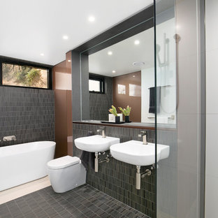 Design ideas for a contemporary master bathroom in Sydney with a one-piece toilet, gray tile, brown walls, a freestanding tub, an open shower, matchstick tile, a wall-mount sink, multi-coloured floor, an open shower, wood benchtops and brown benchtops.