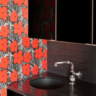Inspiration for a small modern 3/4 single-sink, wallpaper ceiling and wallpaper bathroom remodel in Austin with flat-panel cabinets, black cabinets, red walls, a drop-in sink, black countertops and a built-in vanity