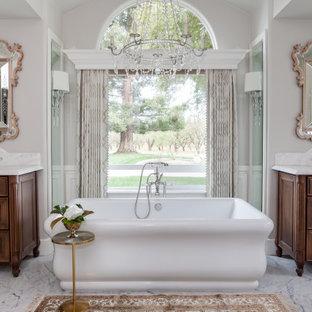 Cette photo montre une grand salle de bain principale chic avec un placard en trompe-l'oeil, des portes de placard en bois brun, une baignoire indépendante, une douche ouverte, un WC à poser, un carrelage blanc, des dalles de pierre, un mur gris, un sol en marbre, un lavabo encastré, un plan de toilette en marbre, un sol blanc, aucune cabine, un plan de toilette blanc, un banc de douche, meuble double vasque, meuble-lavabo sur pied, un plafond en poutres apparentes et du lambris.