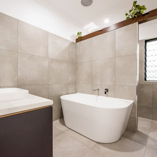 This is an example of a mid-sized contemporary kids bathroom in Other with flat-panel cabinets, grey cabinets, a freestanding tub, an alcove shower, gray tile, ceramic tile, white walls, ceramic floors, a vessel sink, granite benchtops, grey floor, an open shower, white benchtops, a niche, a single vanity and a floating vanity.