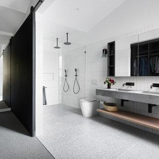Idéer för funkis grått en-suite badrum, med en kantlös dusch, en toalettstol med hel cisternkåpa, vit kakel, ett integrerad handfat, bänkskiva i betong, grått golv och med dusch som är öppen