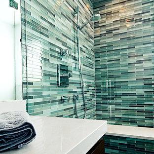 Modelo de cuarto de baño con ducha, minimalista, pequeño, con armarios con paneles lisos, puertas de armario de madera en tonos medios, bañera empotrada, ducha esquinera, sanitario de una pieza, baldosas y/o azulejos verdes, azulejos en listel, paredes blancas, suelo de baldosas de porcelana, lavabo bajoencimera y encimera de cuarcita