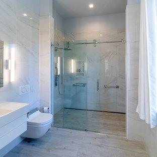 Kleines Modernes Duschbad mit flächenbündigen Schrankfronten, weißen Schränken, bodengleicher Dusche, Bidet, schwarz-weißen Fliesen, farbigen Fliesen, Stäbchenfliesen, bunten Wänden, Porzellan-Bodenfliesen, integriertem Waschbecken, Mineralwerkstoff-Waschtisch, grauem Boden, Schiebetür-Duschabtrennung und weißer Waschtischplatte in New York