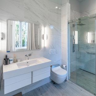 Идея дизайна: маленькая ванная комната в стиле модернизм с плоскими фасадами, белыми фасадами, душем без бортиков, биде, черно-белой плиткой, разноцветной плиткой, удлиненной плиткой, разноцветными стенами, полом из керамогранита, душевой кабиной, монолитной раковиной, столешницей из искусственного камня, серым полом, душем с раздвижными дверями и белой столешницей