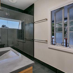 Ispirazione per una stanza da bagno padronale di medie dimensioni con ante in legno chiaro, doccia doppia, piastrelle bianche, pavimento con piastrelle in ceramica, top in acciaio inossidabile, pavimento grigio e porta doccia a battente