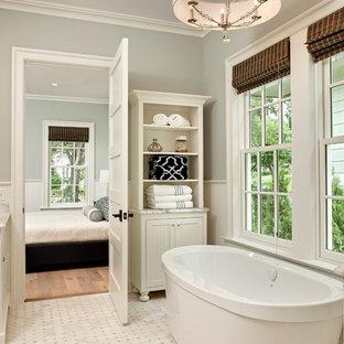 Foto di una grande stanza da bagno padronale costiera con ante a filo, ante bianche, top in marmo, vasca freestanding, piastrelle bianche, piastrelle di vetro, pareti grigie e pavimento in marmo