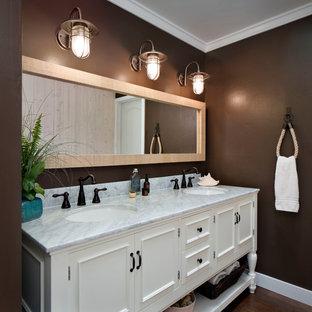 Modelo de cuarto de baño principal, costero, de tamaño medio, con lavabo bajoencimera, puertas de armario blancas, paredes marrones, sanitario de dos piezas, suelo de madera en tonos medios, encimera de mármol y armarios con paneles empotrados
